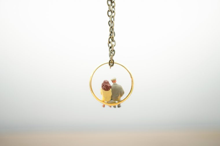 Miniature people: Couple sitting on gold ring