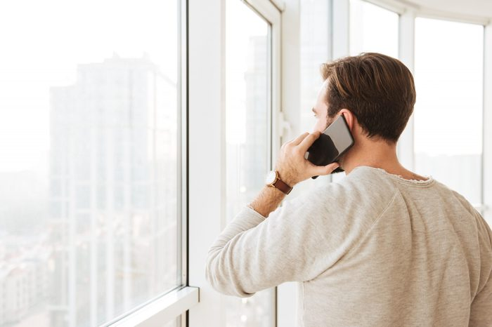 Photo from back of caucasian man with short brown hair looking through window while speaking on black smartphone