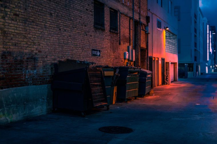 dark empty alley with trash dumpsters. red glowing light.