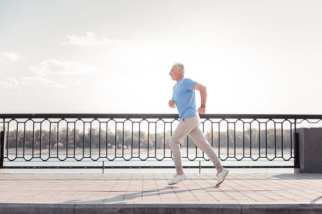 Free of movements. Aged athletic unshaken man being on the quay doing cardio exercises and running.
