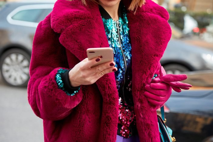 MILAN - FEBRUARY 21: Woman with pink fur coat and sequin jacket looking at smartphone before Alberta Ferretti fashion show, Milan Fashion Week street style on February 21, 2018 in Milan.