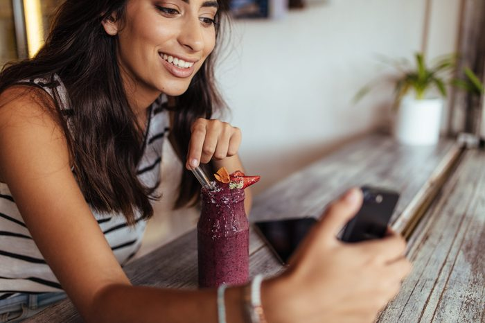 Woman taking a selfie with a smoothie using a mobile phone for her food blog. Food blogger shooting photos for her blog at home.