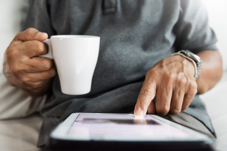 Close up Senior male hands using digital tablet. Happy Asian Man sitting on sofa and holding cup of coffee.