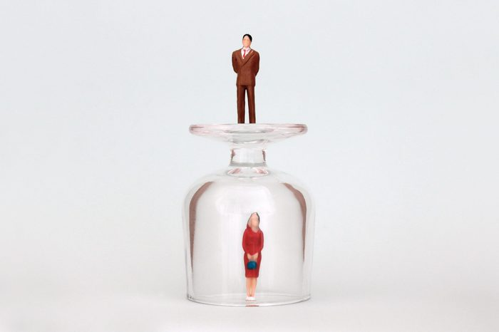 A miniature woman in a glass cup and a miniature man on top of a glass cup. The concept of the gender promotion gap.