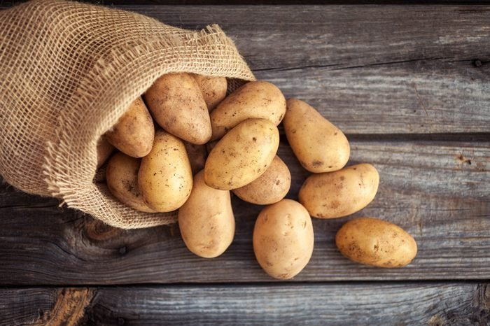 Raw potato food . Fresh potatoes in an old sack on wooden background. Top view