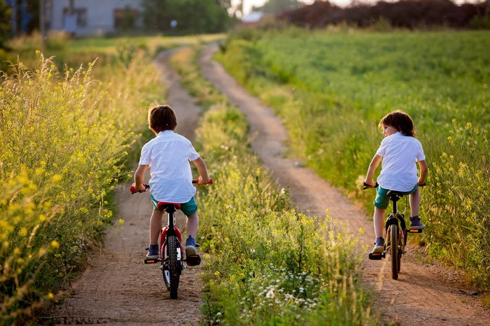 Sporty children, boy brothers, riding bikes on a rural landscape together on sunset