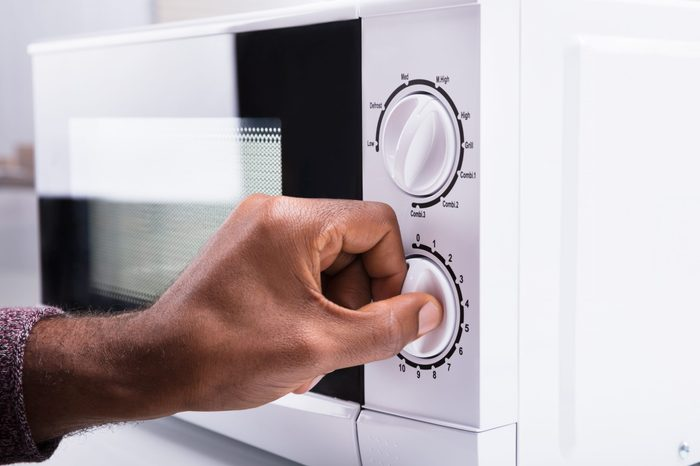 Close-up Of A Man's Hand Adjusting Temperature Of Microwave Oven
