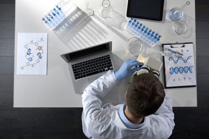 Scientist viewing samples under microscope, research for scientific article