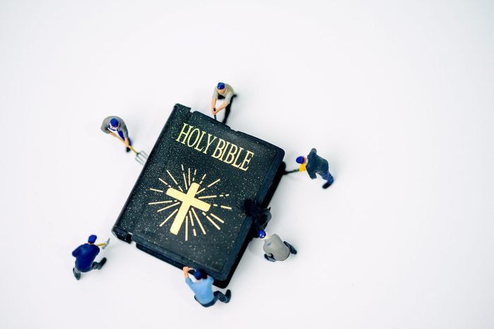 Miniature people : Worker try to fix and open Holy bible on white background
