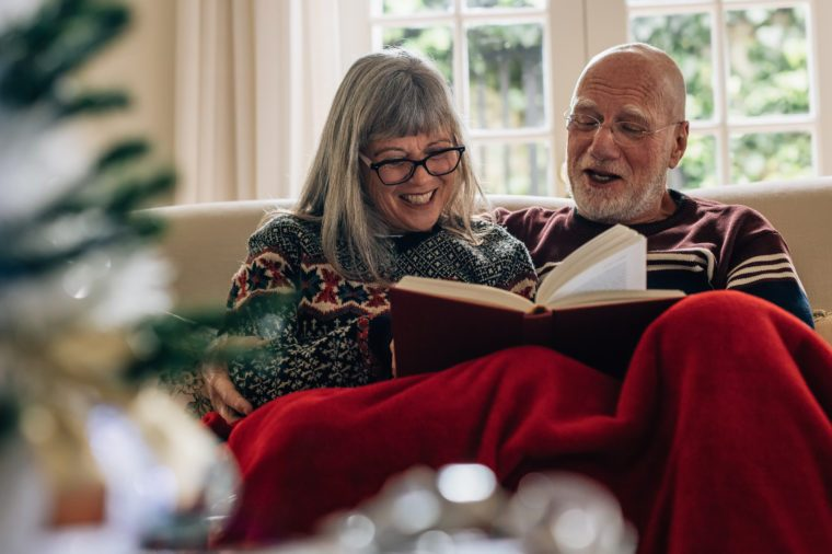 Happy senior man and woman reading a book and smiling. Old couple spending time together reading a book sitting on couch at home.