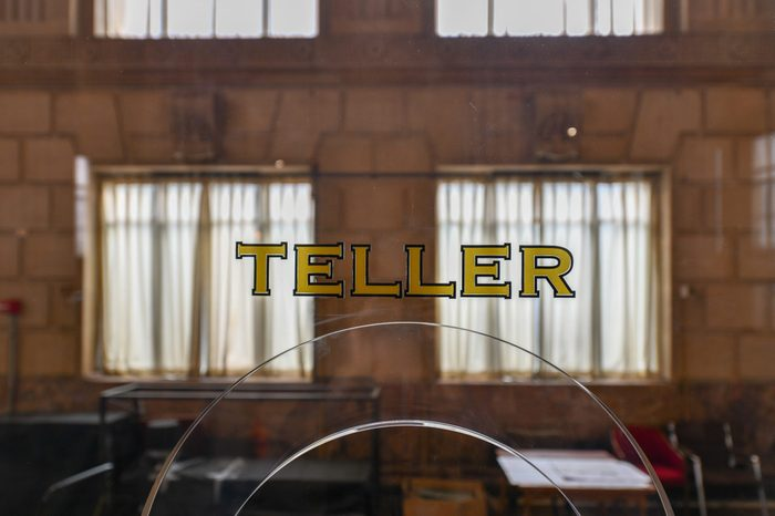 Old fashioned bank teller window sign in a classically styled building.