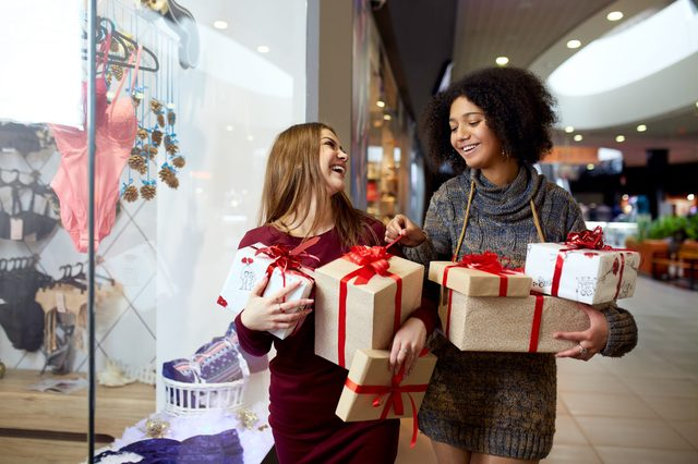 Two mixed race women with gift boxes in hands near storewindow. Multi ethnic girls smiling with presents on christmas new year sale. Caucasian and african american females buy presents for holidays.
