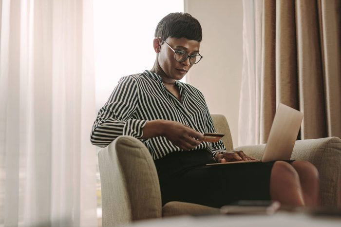 woman in hotel room with laptop and credit card
