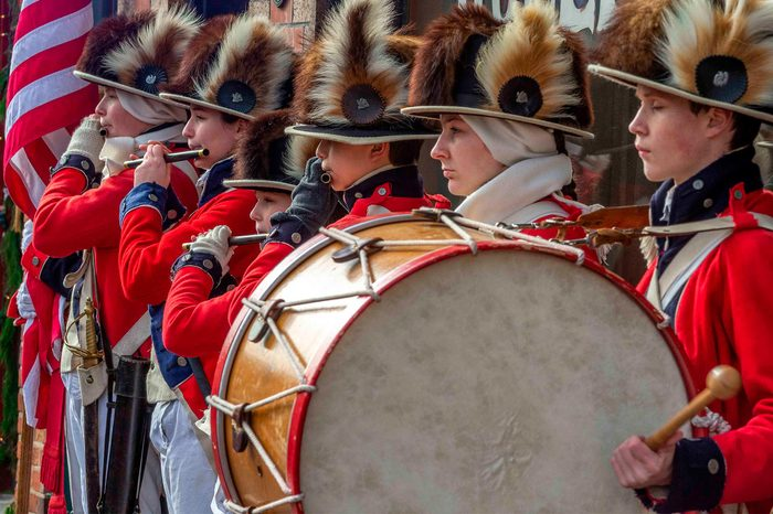 Saint Charles, MO--Dec 22, 2018; actors dressed up in red white and blue Historic US Army pipe and drum uniforms music during downtown seasonal festivities