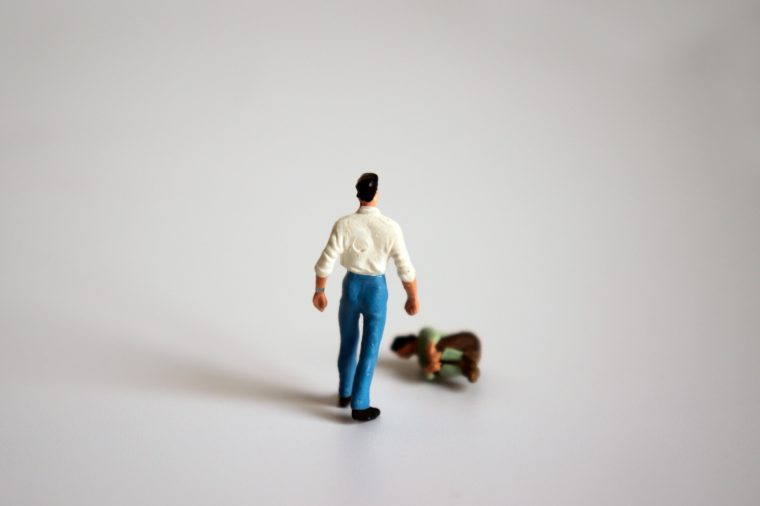 A miniature man is standing and a miniature woman is falling down