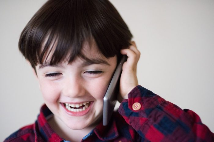 adorable happy laughing little caucasian boy in plaid shirt talking by cell phone