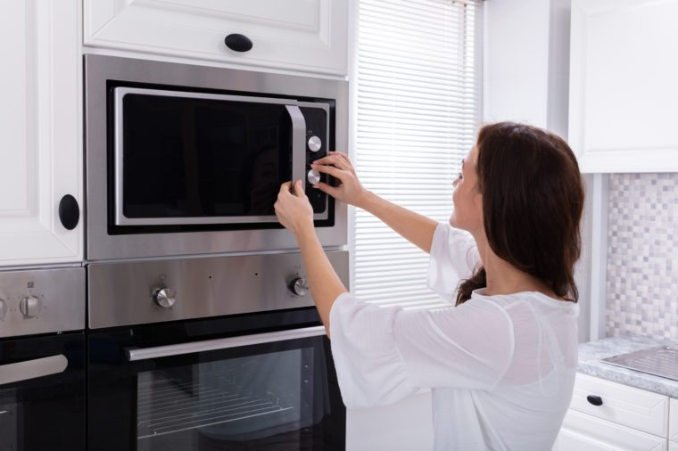 Side View Of A Young Woman Using Microwave Oven In Kitchen
