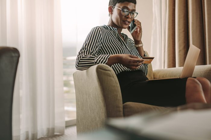 Female CEO sitting in hotel room with laptop and credit card talking over cell phone. African businesswoman doing online bill payments from hotel room.