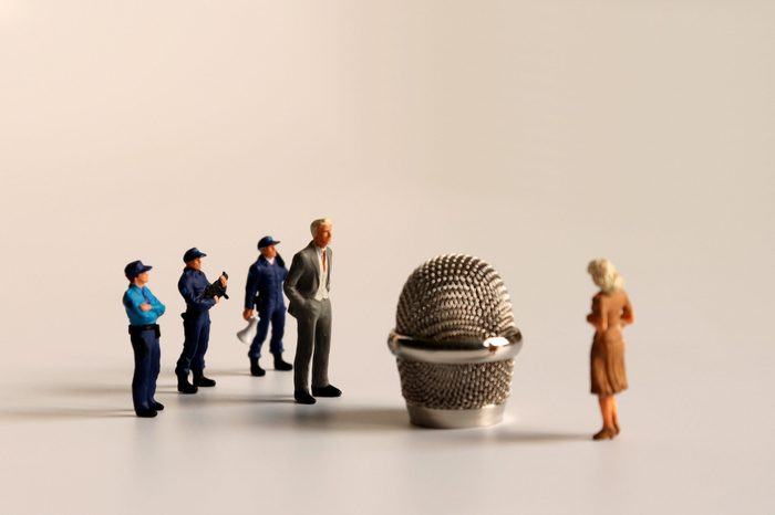 Miniature people standing around a microphone head