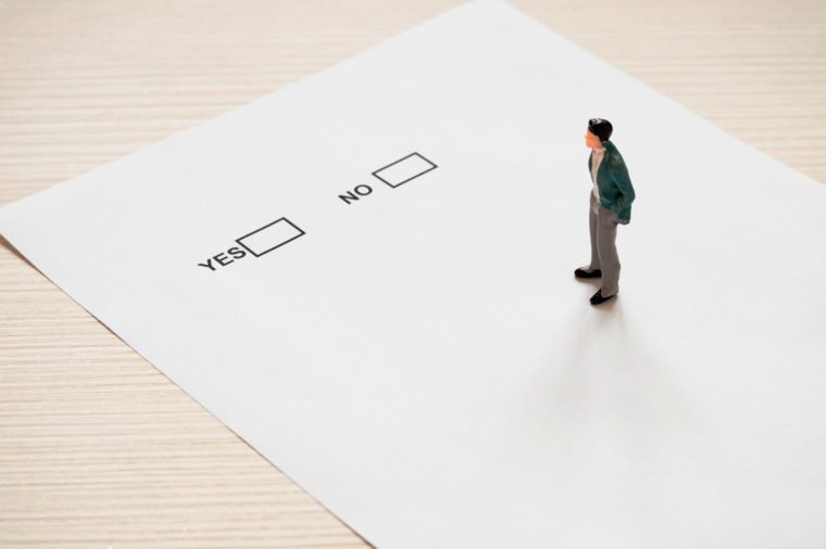 miniature buisenessman standing on paper sheet with yes or no note