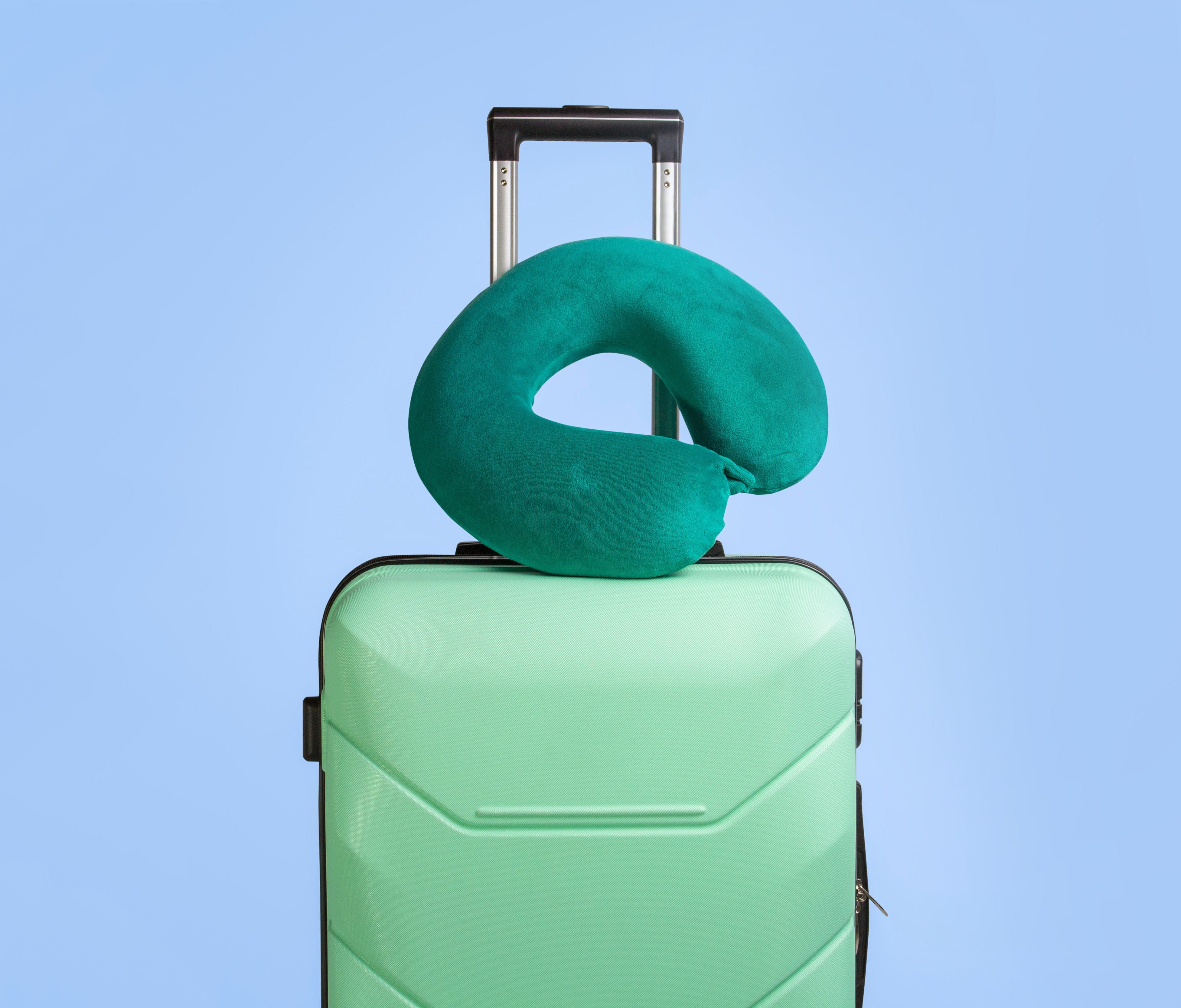 Plastic suitcase and travel pillow on a blue background. Concept of travel, business trips, trips to visit friends and relatives; Shutterstock ID 1339295669; Job (TFH, TOH, RD, BNB, CWM, CM): -