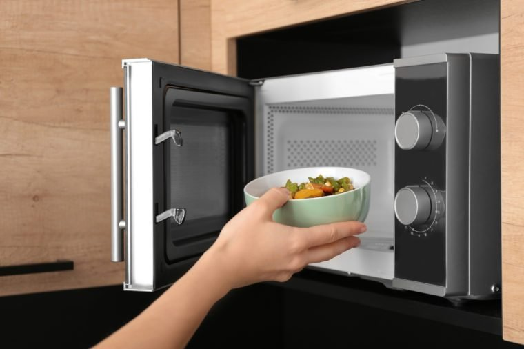 Young woman using microwave oven in kitchen