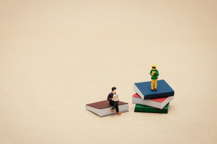 miniature people sitting on small stacks of books