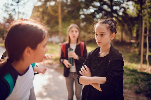 Girl wearing black hoodie bullying girl at schoolyard
