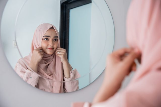 muslim woman fix and make up her self looking at the mirror