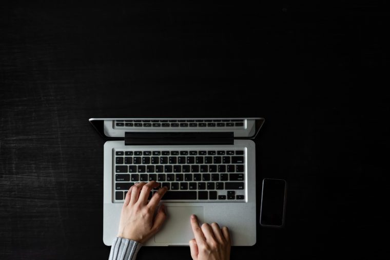 op view of Designer hand working with laptop computer on dark in modern office