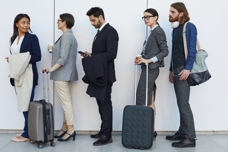 Group of serious boring young multi-ethnic people with bags and luggage standing in line while passing through airport security check