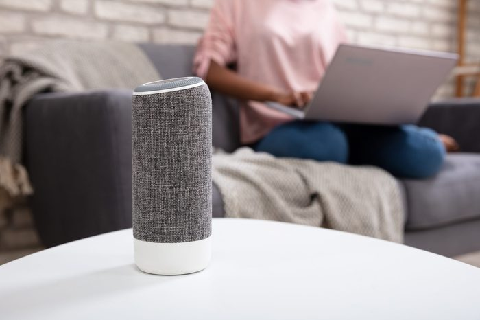 Woman With Laptop Using Voice Assistant Speaker At Home