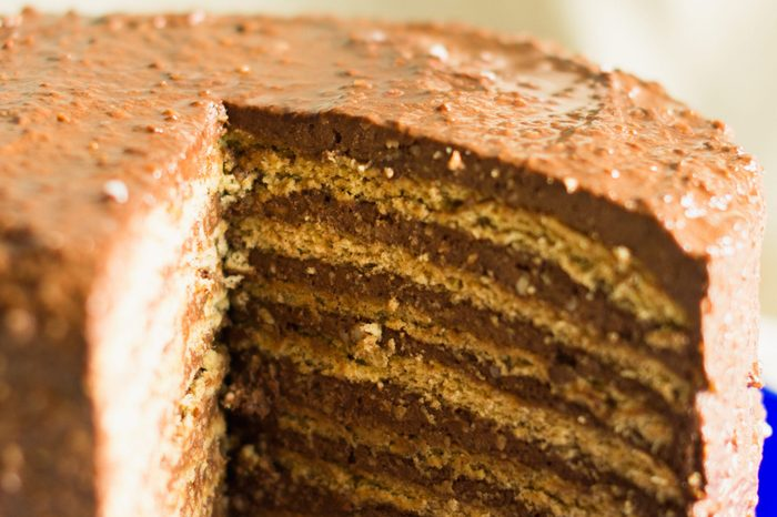 layered cake with chocolate-nut cream in a blue dish on a linen tablecloth