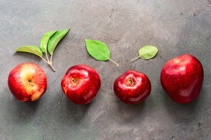 Ripe red apples and green leaves are arranged in a row on a dark rustic background. Flat lay, copy space, overhead
