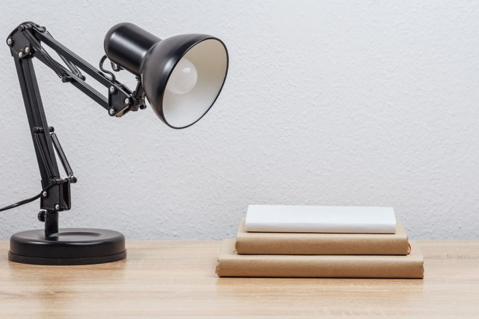 Table lamp and books on the office table. Light background.
