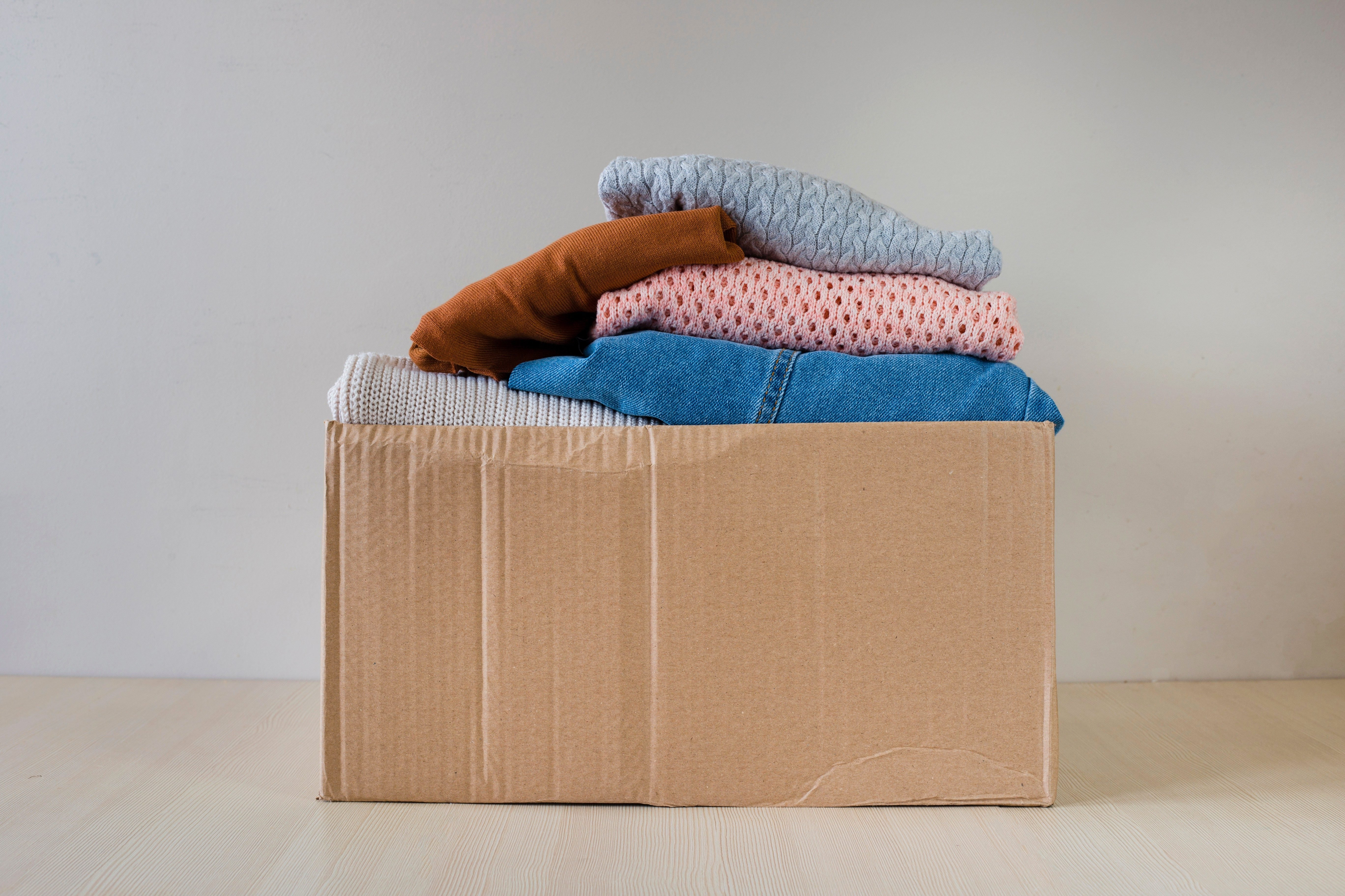 Cardboard old box with clothes on wooden table. Concept for charity, free clothes giving service. Neutral, pastel colors background. Image.<br /> ; Shutterstock ID 1440468068; Job (TFH, TOH, RD, BNB, CWM, CM): RD