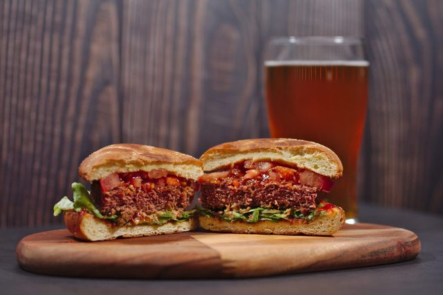 vegan plant based burger split in half served on rustic cutting board with beer