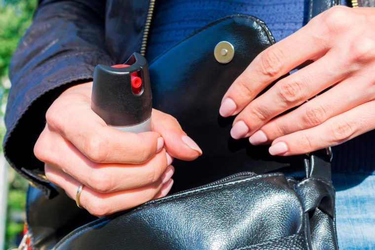 A young woman pulls a can of tear gas or bottle of pepper spray out of her purse. Means of self-defense. Selective focus, close-up.