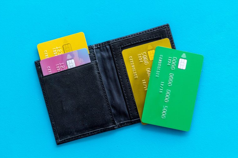 business with credit cards and wallet on office desk blue background top view