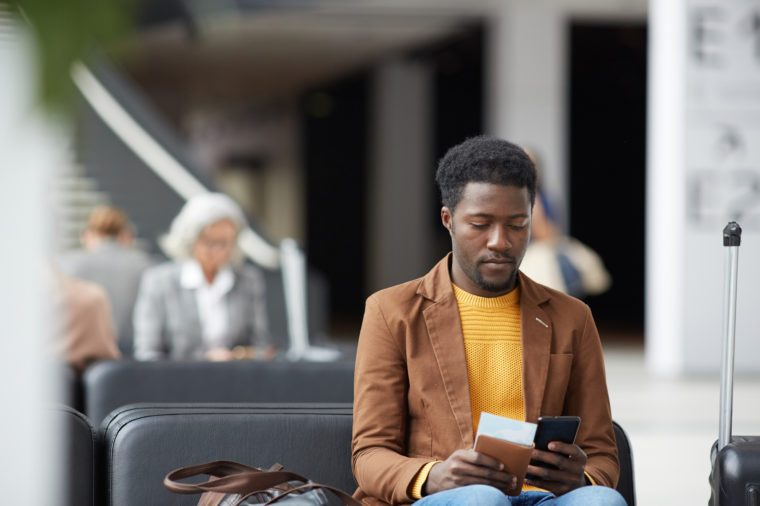 Serious pensive young black man with beard sitting in airport and communicating via online app on phone
