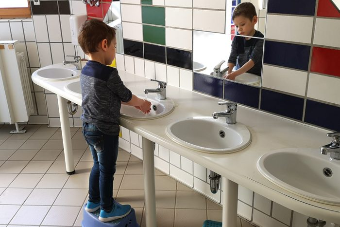 3-year-old little boy, dressed in jeans and dark blue longsleeve, washes his hands himself in the sink in the room of the children's toilet, standing in front of the morror. Side view. Selective focus
