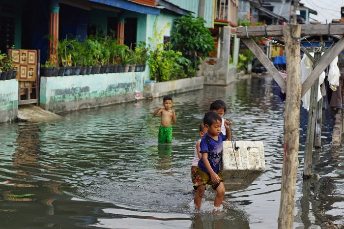 Medan, Indonesia - April 15,2017 : Children play in front of their flooded house.Children enjoy flooded streets to bathe with big health risks