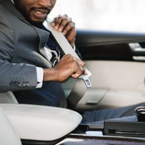 Car safety. Business man fastening seat belt in auto, driving to work, copy space