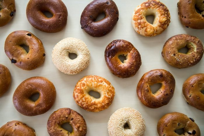 Selection of various flavors of fresh bagels on a neutral wood table background