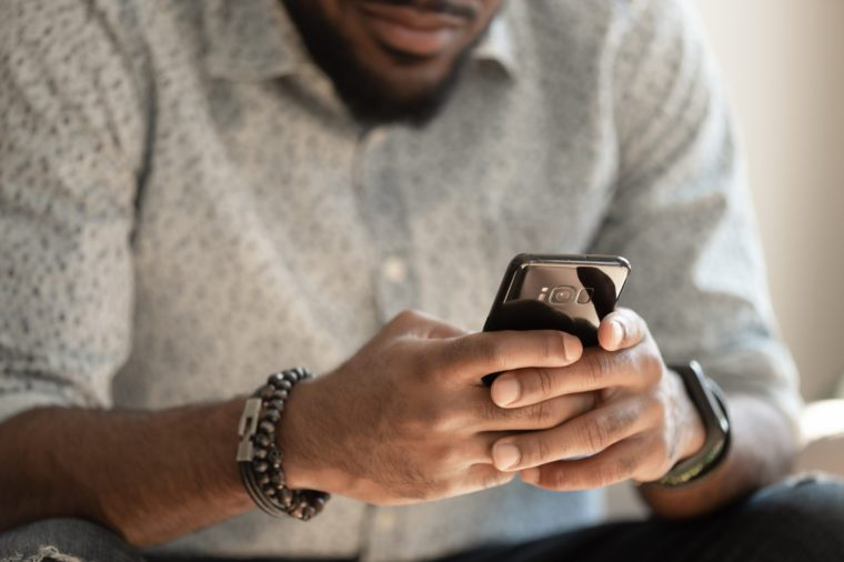 Close up young african american man sitting on couch, holding smartphone in hands, typing message, posting in social media, chatting with friends or relatives, playing online game, doing purchases.