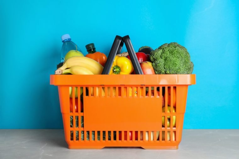 Shopping basket with grocery products on grey table against light blue background
