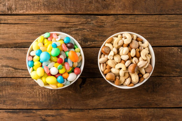 Comparison of healthy and unhealthy snacks. Mixed nuts and sweet in bowls on wooden background