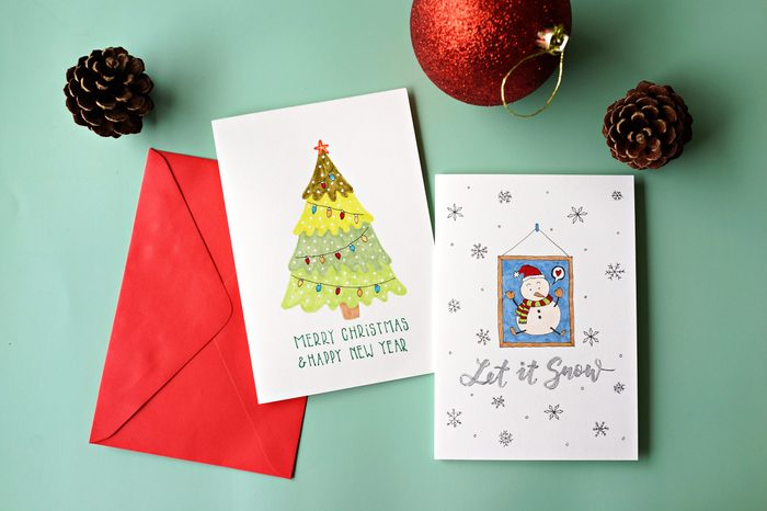 Top view hand drawn Christmas greeting cards with envelope and Christmas decoration.