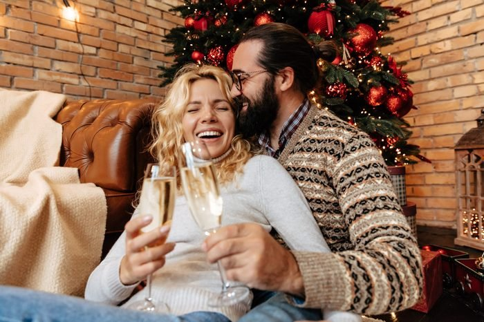 Christmas. Couple. Home. Togetherness. Man and woman are drinking champagne, hugging and laughing near the Christmas tree