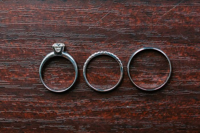 Three rings on wooden background. Engagement ring and two wedding bands on wooden table. White gold wedding jewelry.